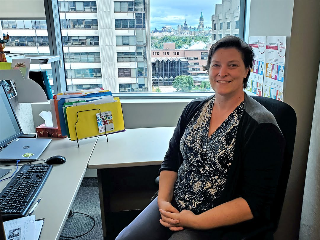 Rachel Collishaw at her desk at Elections Canada with Parliament in the background